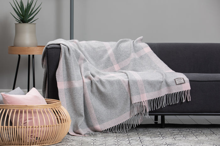 Foxford's Pink and Pearl Grey Windowpane Cashmere Throw draped across a Grey Couch