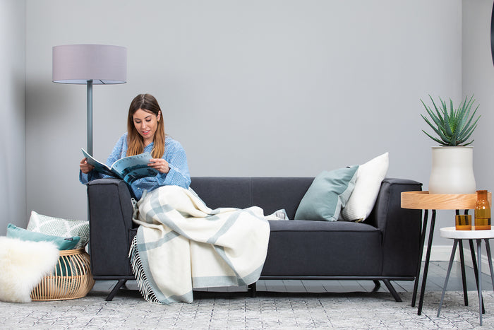 Women curled up reading on a couch wrapped in Foxford's Sage and White Windowpane Cashmere Throw