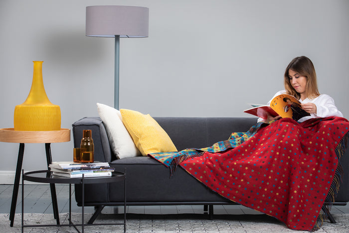 Foxford's Red Multi Spot Lambswool Throw draped across women reading the magazine on the grey couch