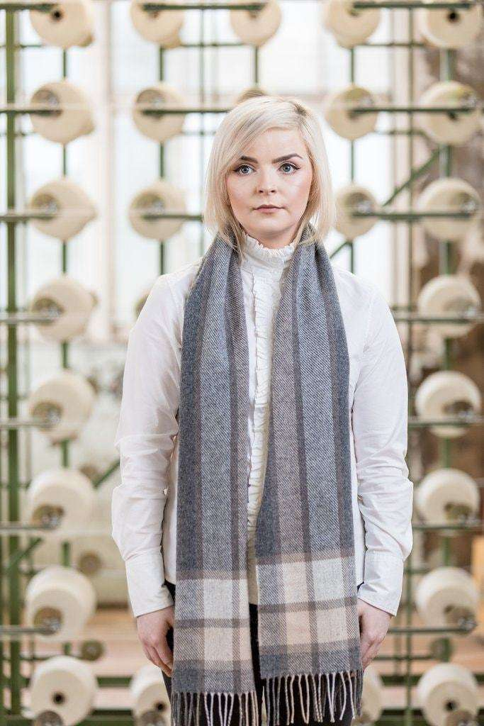 Woman wearing Foxford's Grey Check Border Scarf in Woollen Mill