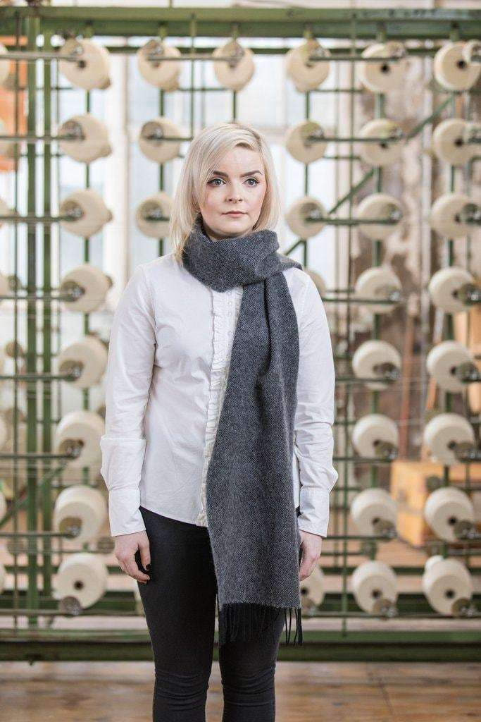 Woman wearing Foxford's Classic Grey Herringbone Scarf in Woollen Mill