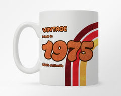 White coffee mug with customization 1970 birth year, with a brown, yellow, and red rainbow graphic underneath