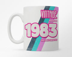 White coffee mug with customization 1980 birth year, with a bright purple, turquoise, and pink rainbow stripe underneath