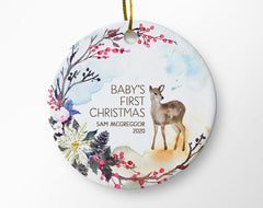 "White ceramic round ornament with ""Baby's first Christmas"", a deer, and a floral border"