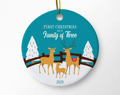 "Blue ceramic round ornament with ""First Christmas as a family of three"" printed above a drawing of three deer in the snow"