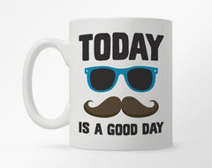 "White coffee mug with ""today is a good day"" in bold black print, with sunglasses and mustache"