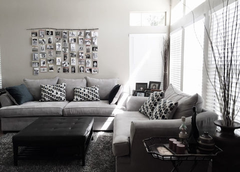 A couch with throw pillows and wall art on the wall.