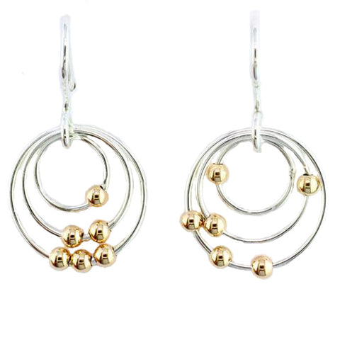 Dangling Sterling Silver circles hold moving 14 Karat Yellow Gold beads.