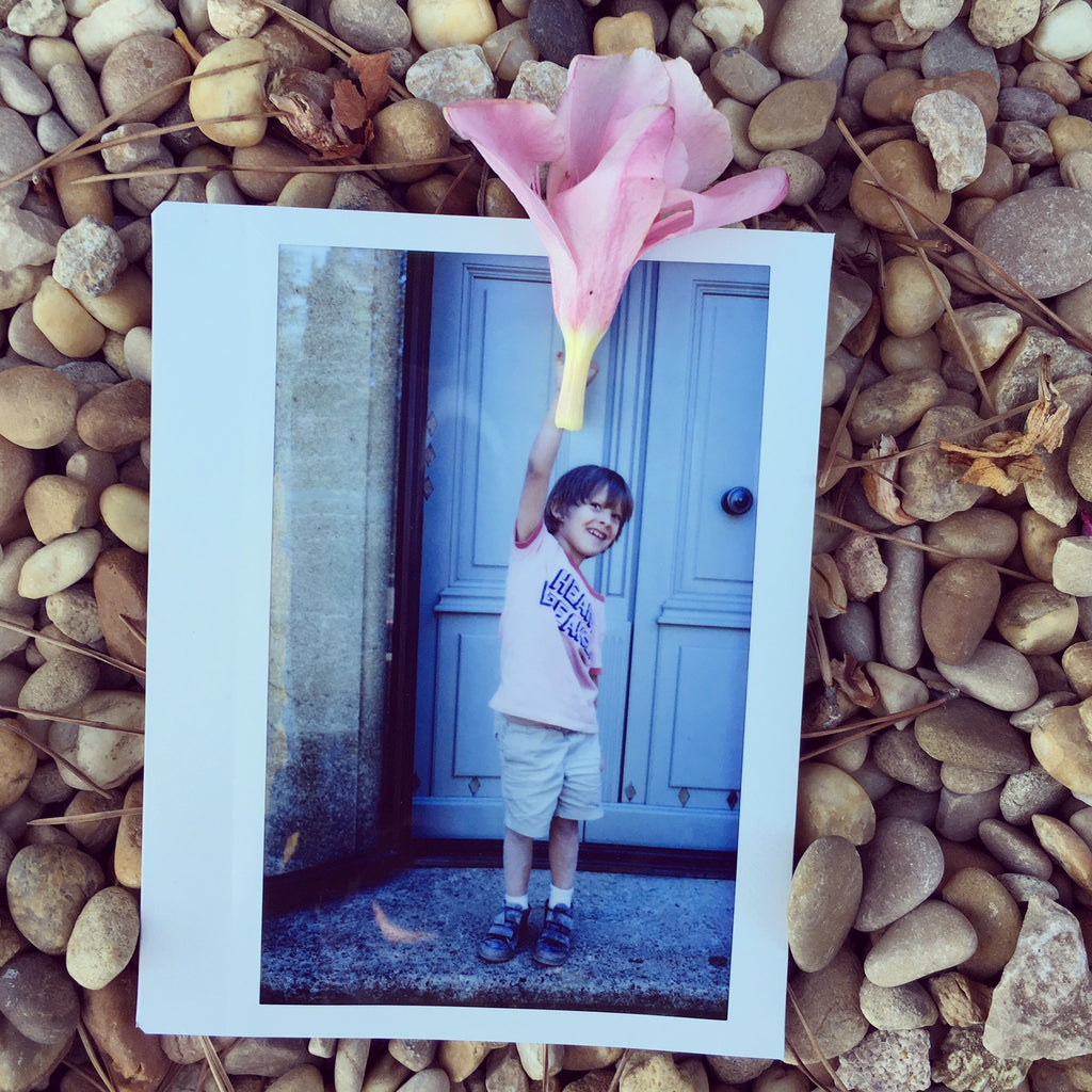 Polaroid Picture of Child Holding a Flower