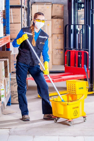 Warehouse cleaning personal with mop and mask