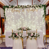 White tulle backdrop with artificial white flower foliage & fairy lights (2.5m by 3m)