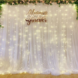 White tulle backdrop with artificial blush flower foliage & fairy lights (2.5m by 3m)