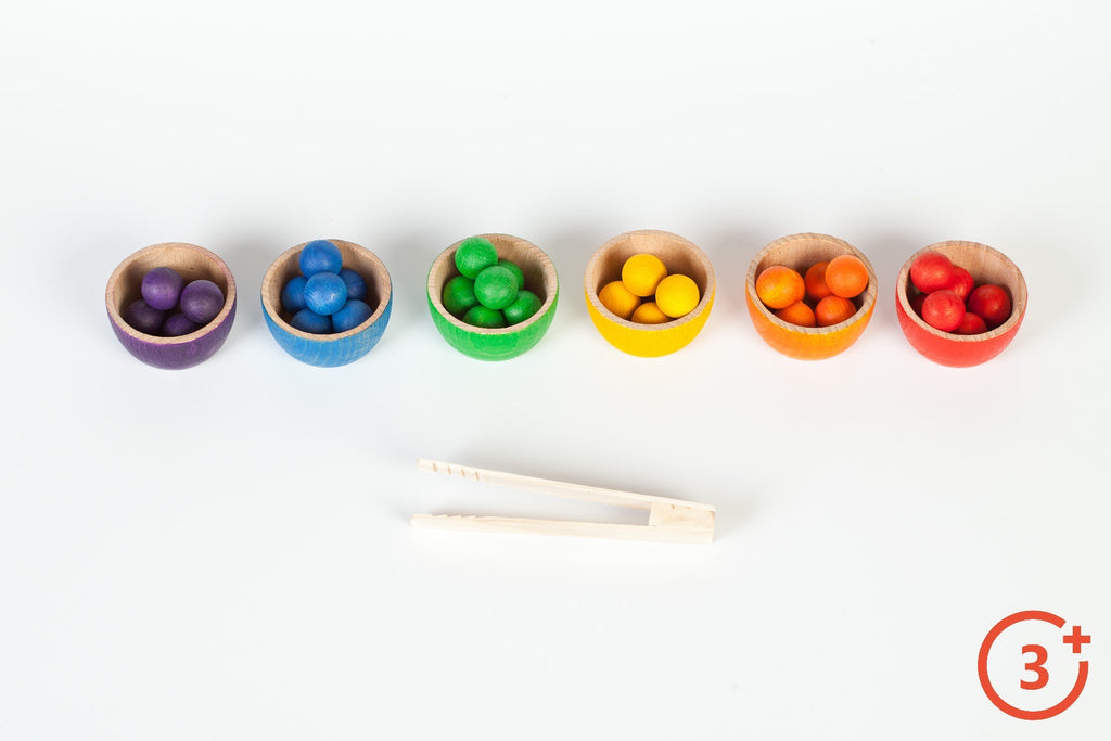6 rainbow bowls with wooden balls in red, orange, yellow, green, blue and purple. Includes wooden natural tongs.