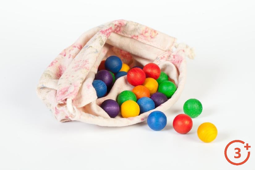 Small rainbow coloured wooden spheres in cotton bag