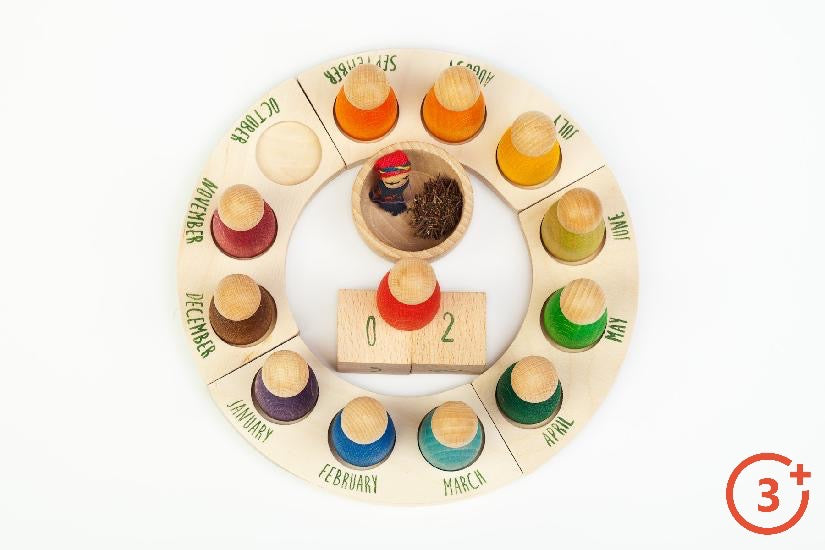 4 quarter wood pieces make up a circle calendar. Each quarter piece has three months and three spots for coordinating included nins.  Calendar comes with number blocks for date and wooden bowl for decor.