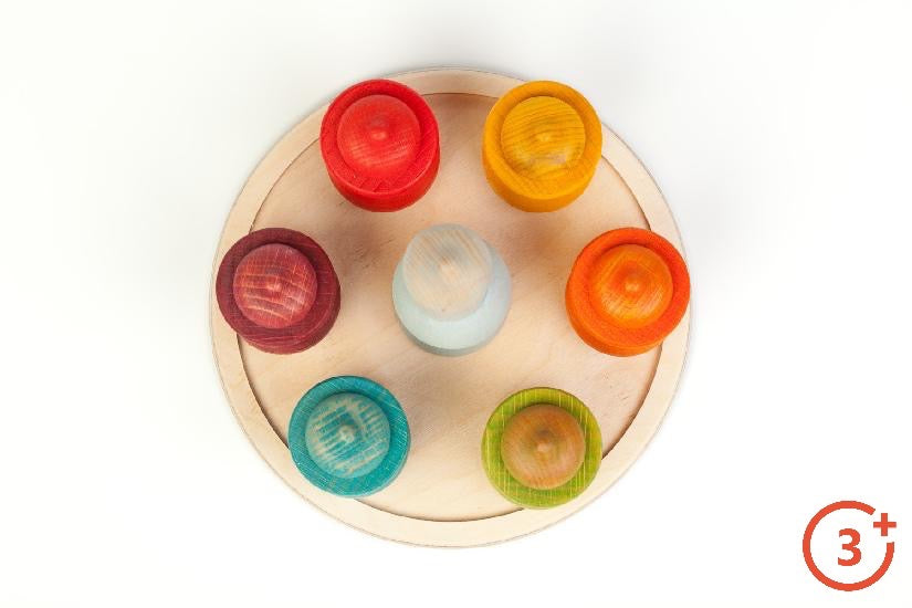 top view of grapat's 7 moons weekly calendar showcasing the 7 coloured acorn nins on wooden round tray