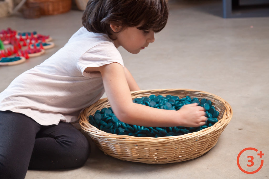 Child playing with small dark blue wooden coins in wicker basket.