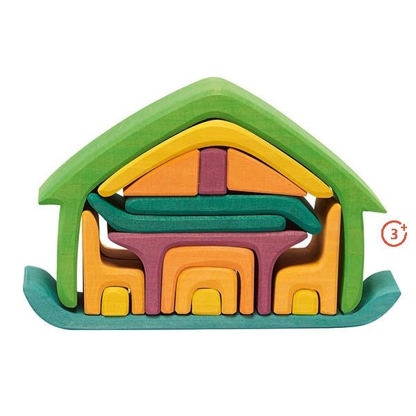 green yellow maroon and dark green nesting house. 17 wooden shapes nestled into a larger house shape includes chair pieces, table, and multifunctional shapes for open ended play