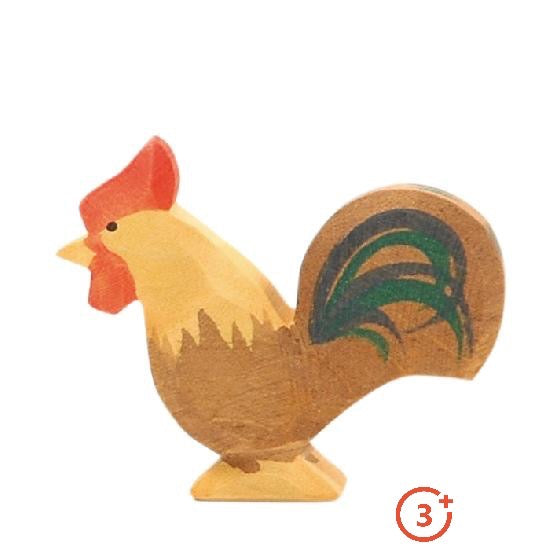 wooden rooster with medium brown and light golden accents. The tail is detailed with blue and green feathers.