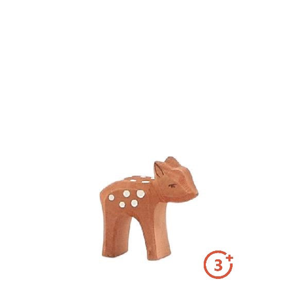 medium brown small fawn standing with white spots and dark brown detailing for ears, eyes and nose.