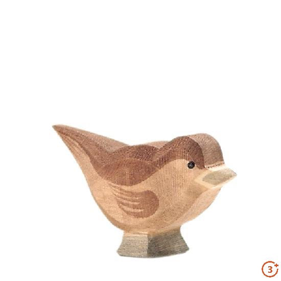 medium warm brown sparrow bird with grey feet and beak and black detail for eyes. Slightly bent over looking up.
