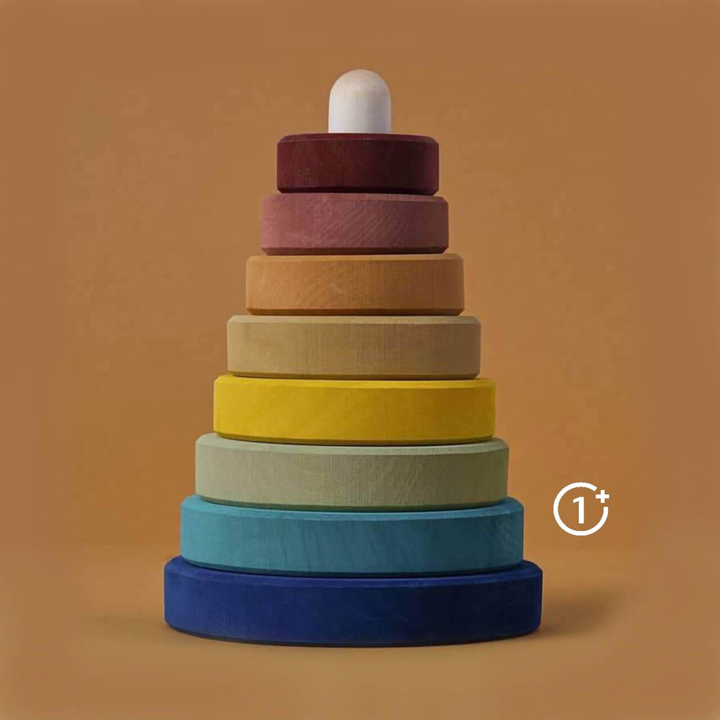 8 wooden ring stacker from navy blue to deep Burgundy and earth tones in between. Stacked on white wooden base. Raduga Grez Earth Stacker.