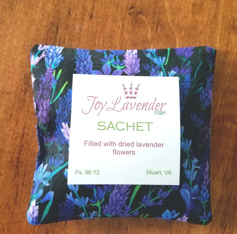 4 inch square sachet made from a cotton lavender print fabric with a black background and flowers in shades of blue and purple.   Filled with dried lavender flowers.