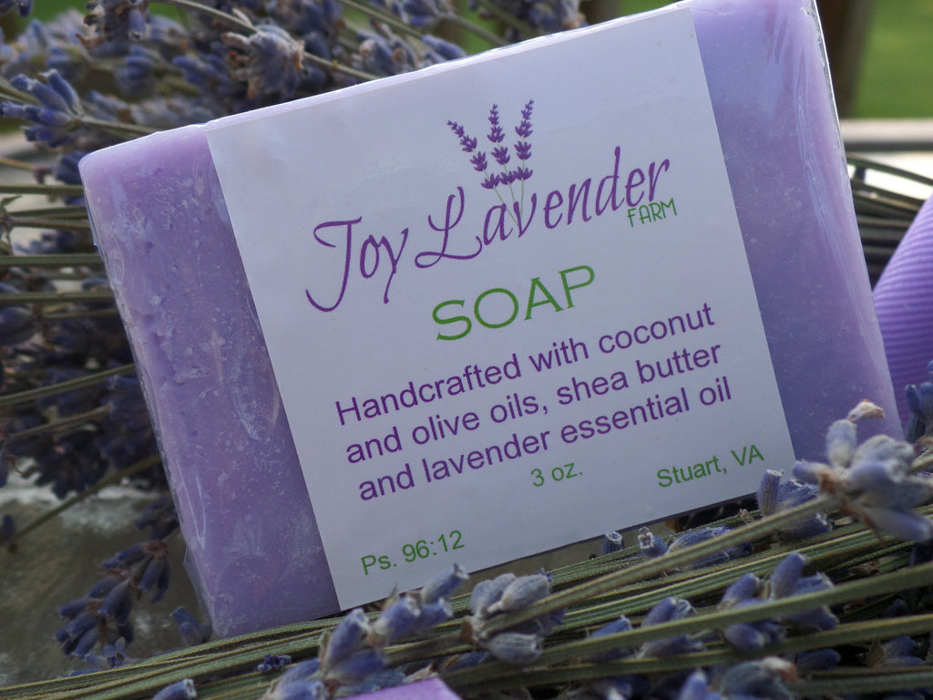 Light purple bar of Lavender soap wrapped in clear plastic wuth a white label.