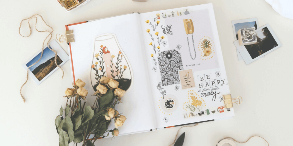 White background with scrapbook and dried white roses