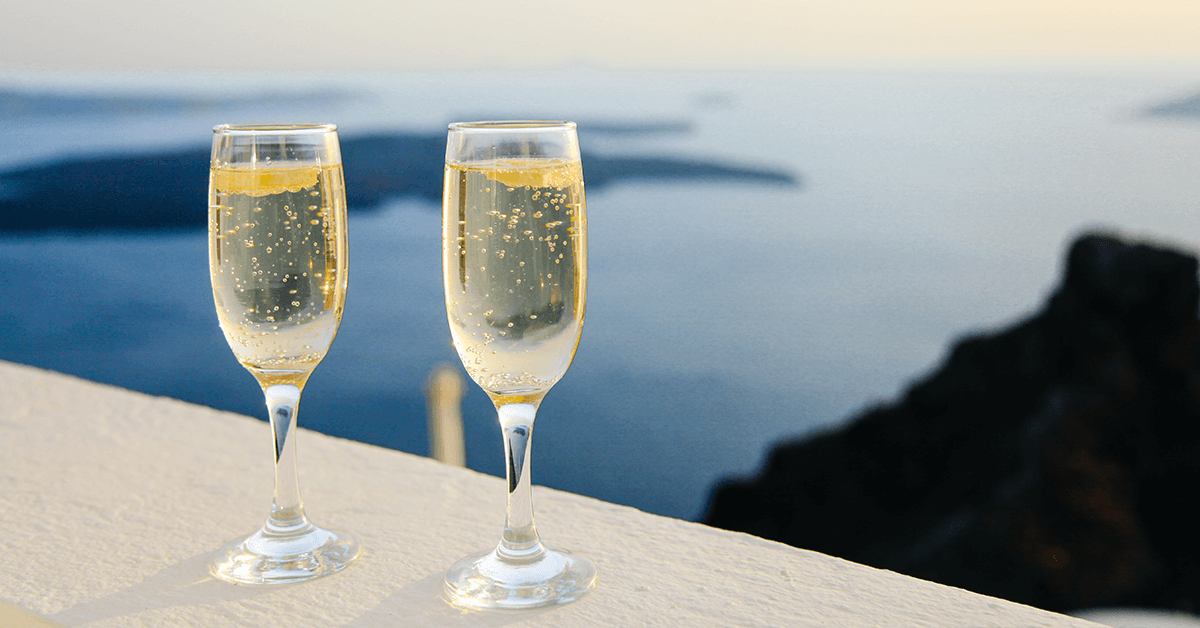 Two glasses of champagne in front of an ocean view