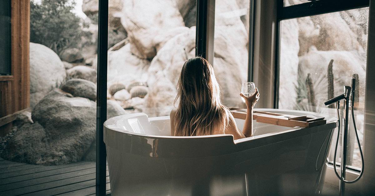 Lady sitting in bath looking at white rock scenery