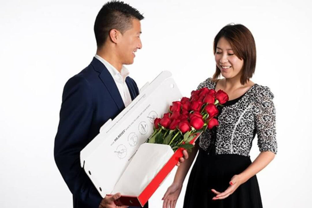 man giving his lover a bunch of long stem red roses in a long box
