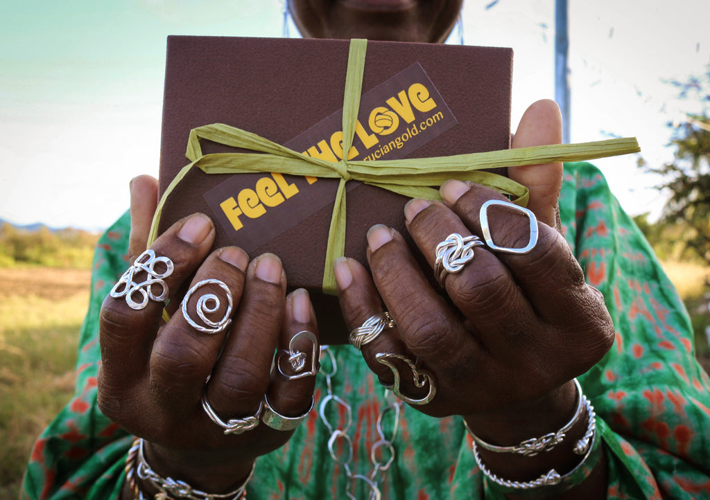 A woman's hands covered in silver rings hold a gift box.