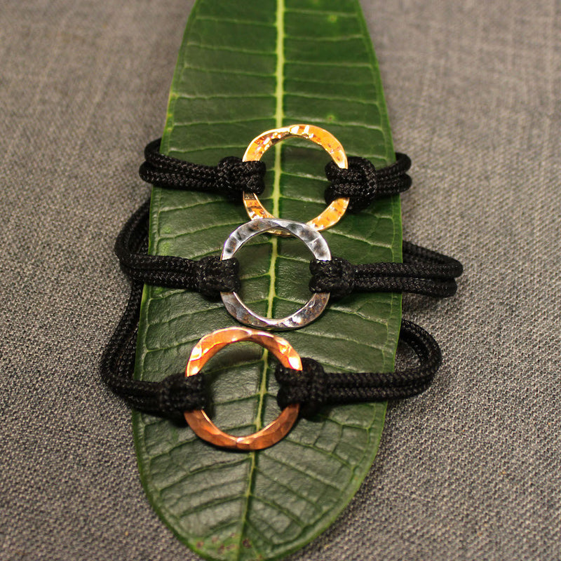Black nylon adjustable cord bracelet with circular design in center available in copper, sterling silver and 14k gold.