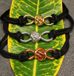 3 adjustable black nylon cord bracelets with copper, 14k gold and sterling silver infinity shaped Crucian knot charms.