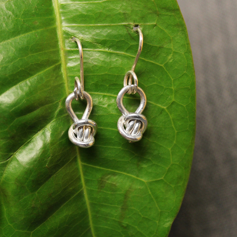 Sterling silver charm earrings for child with small Crucian knot design.