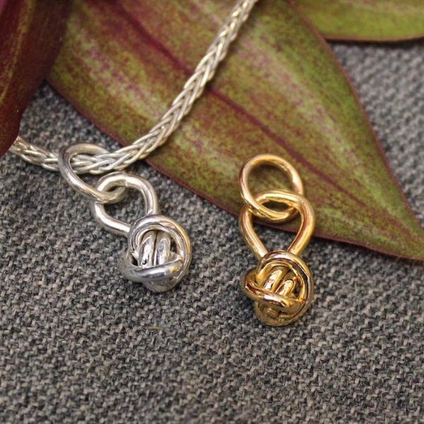 Sterling silver charm and 14k gold charm with ball shaped Crucian knot design.