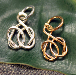 Sterling silver and 14k gold charms with friendship knot design.