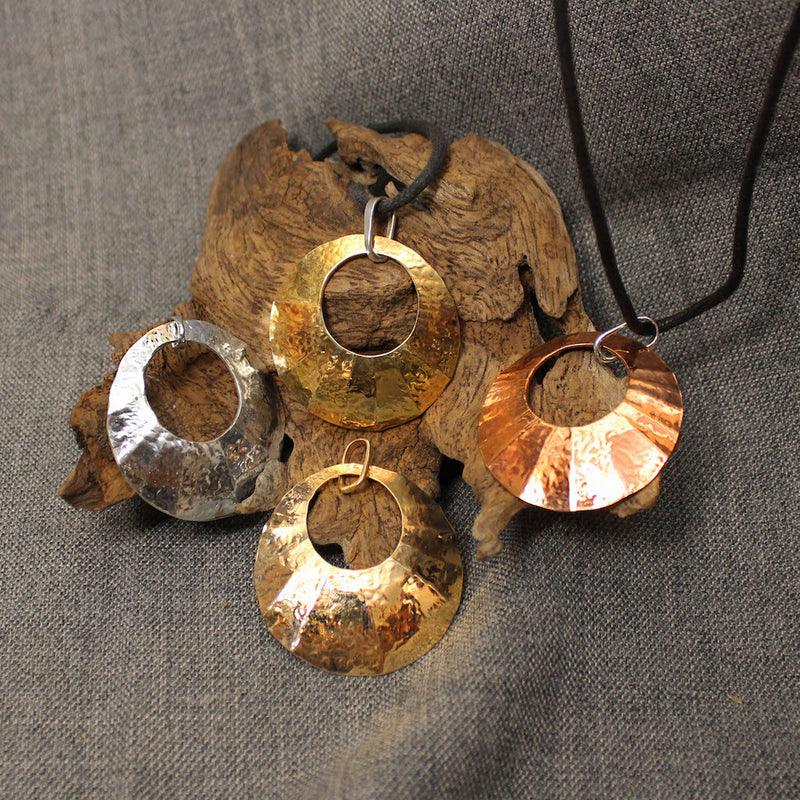 Brass, copper, sterling silver and 14 gold hammered circular pendants.