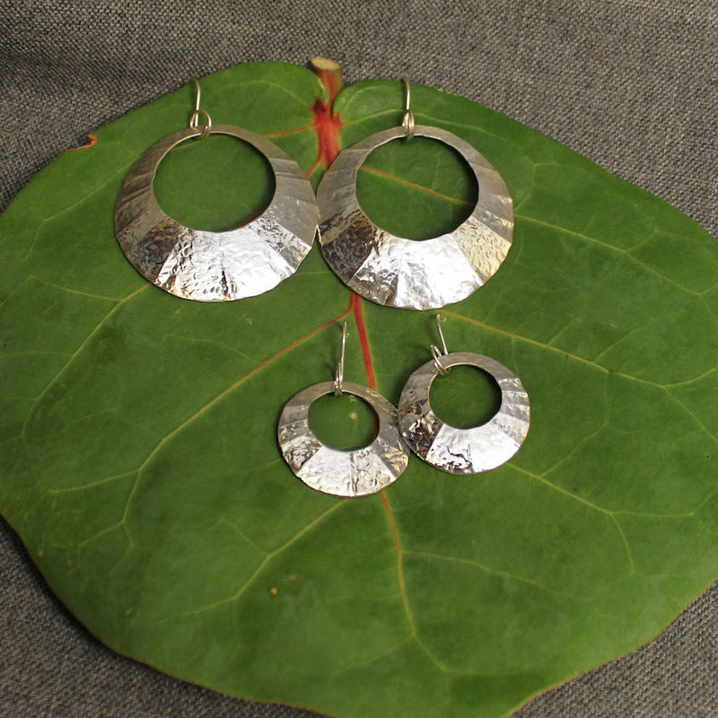 Small and large sterling silver hammered circular earrings.