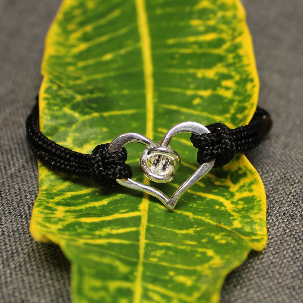 Black adjustable nylon cord bracelet with sterling silver heart and love knot piece in center.
