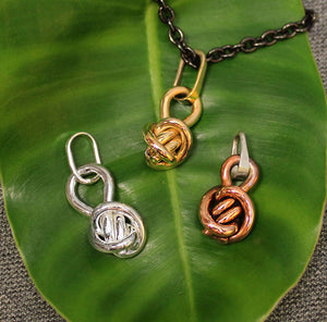 Copper, Sterling silver and 14k gold ball shaped pendants with Crucian knot design.