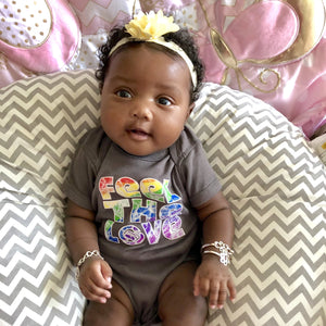 "Happy baby girl wearing gray cotton onesie with a rainbow ""Feel The Love"" design"