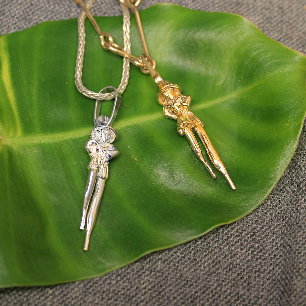 Sterling silver and 14k gold Moko Jumbie pendants.