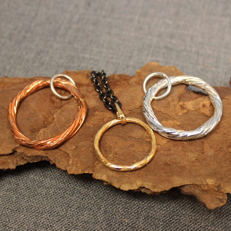 Handcrafted copper, sterling silver and 14k gold hoop pendants.