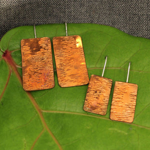 Small and medium sized rectangular hammered copper earrings.