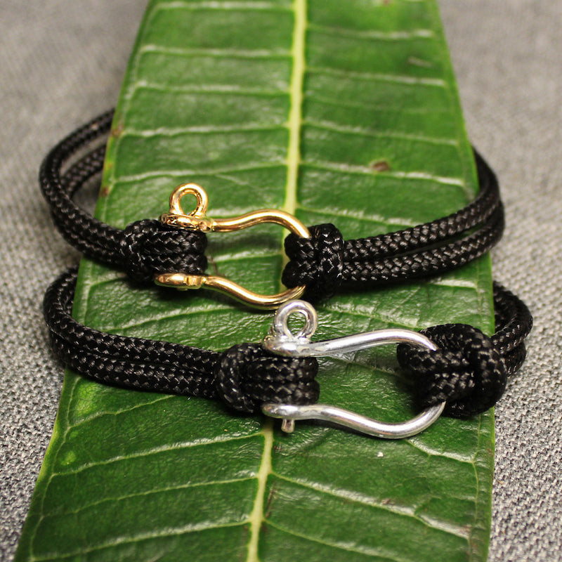 Sterling silver and 14k gold Sailor's Shackle adjustable black nylon cord bracelet.