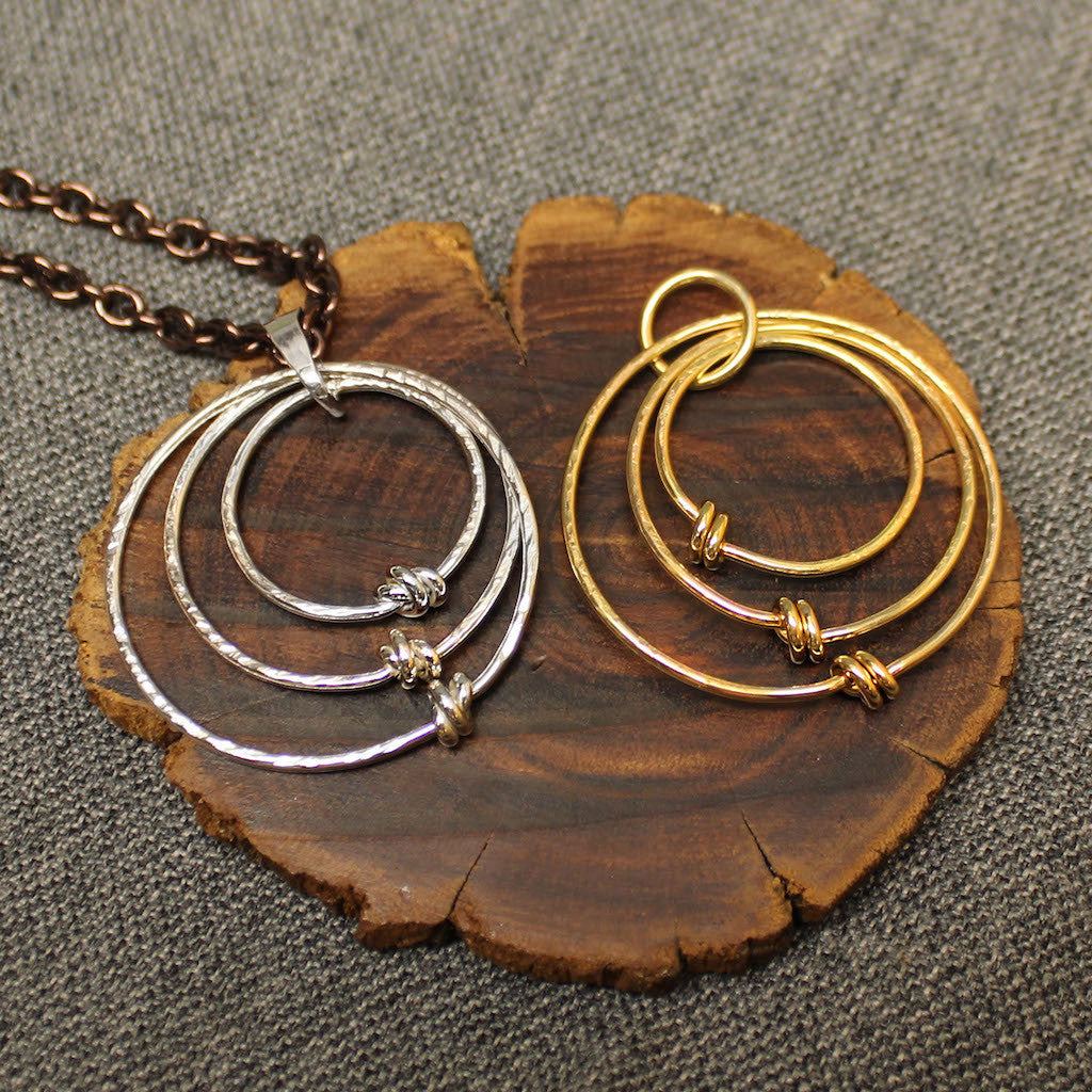 Sterling silver and 14k gold pendants with 3 tiered hoops.