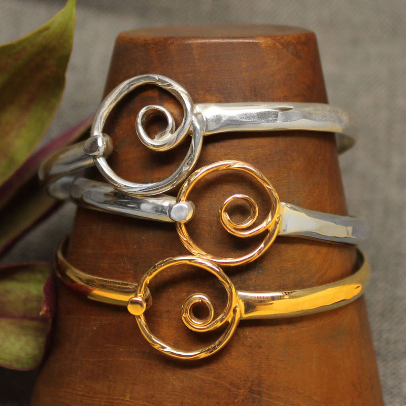 Sterling silver, 14k gold and 2-tone latching bracelets with spiral design in center.