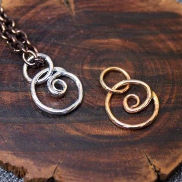 Sterling silver and 14k gold spiral charms.